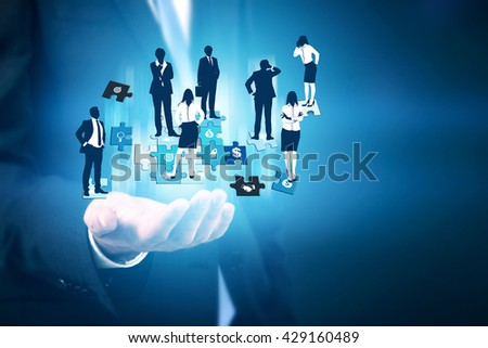 Businessman hand holding abstract image of businesspeople on puzzle pieces. Concept of teamwork and partnership - stock photo