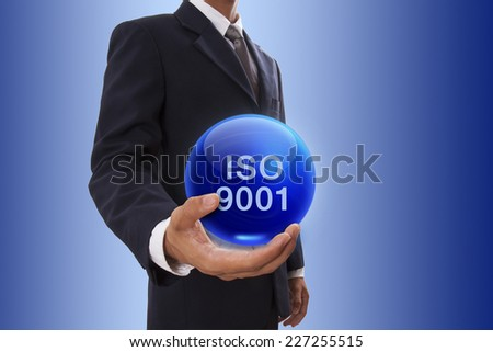 Businessman hand holding blue crystal ball with iso 9001 word. - stock photo