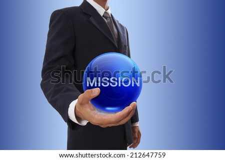 Businessman hand holding blue crystal ball with mission word. - stock photo
