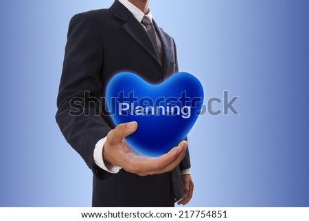 Businessman hand holding blue heart bubble with planning word  - stock photo