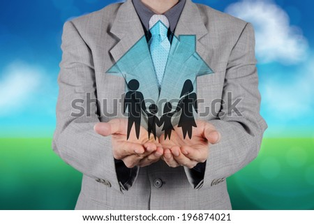 businessman hand holding 3d house with family icon on nature background as insurance concept  - stock photo