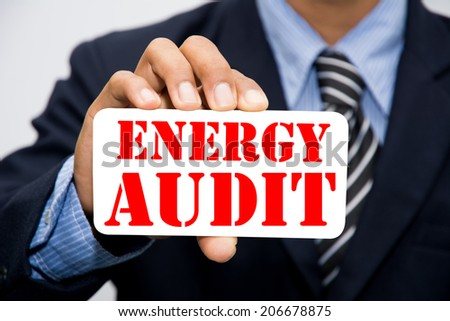 Businessman hand holding ENERGY AUDIT concept  - stock photo