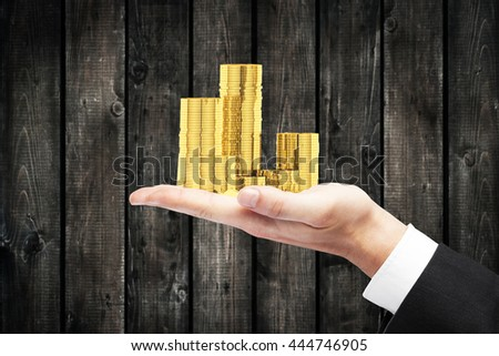 Businessman hand holding golden coin stacks on wooden plank wall background - stock photo