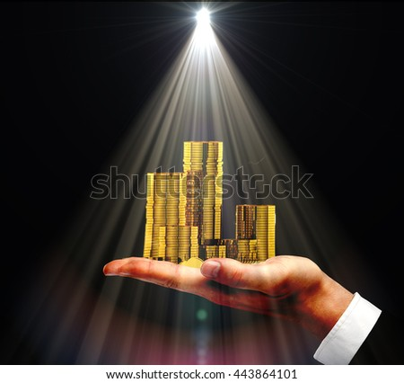 Businessman hand holding golden coin stacks with spotlight above on dark background - stock photo