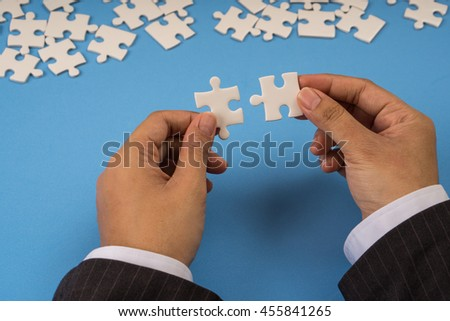 businessman hand holding jigsaw puzzle connection, blue background
