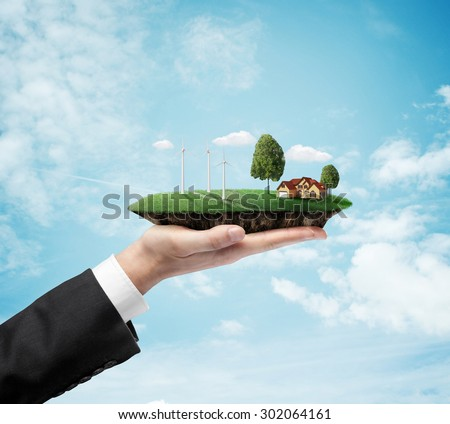 businessman hand holding landscape with eco wind turbine - stock photo