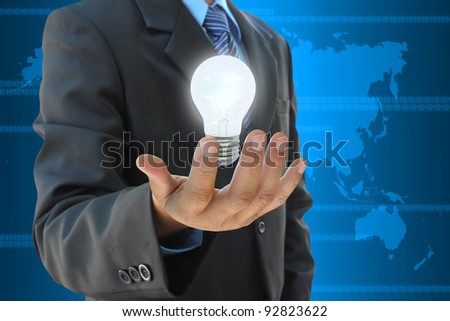 businessman hand holding light bulb - stock photo