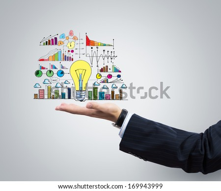 Businessman hand holding light bulb in palm - stock photo