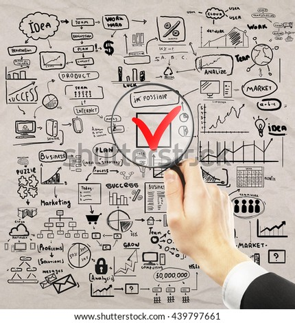 Businessman hand holding magnifier over red checkmark with business drawings around on crumpled paper background. Nothing is impossible concept