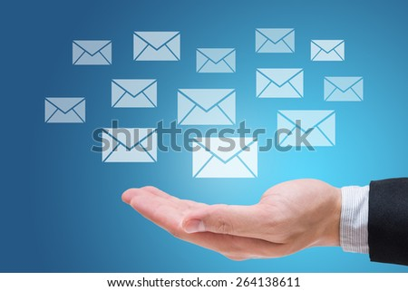 Businessman hand holding messages or letter isolated on blue background - stock photo