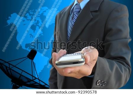 businessman hand holding mobile phone and satellite dish antennas - stock photo