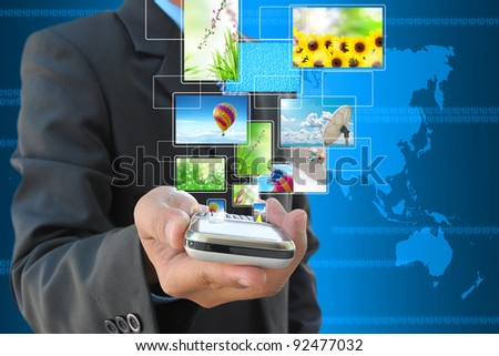 businessman hand holding mobile phone and streaming images virtual buttons - stock photo