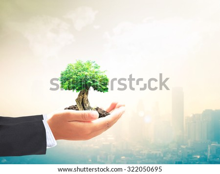 Businessman hand holding plant with soil on blurred warm city sunrise over world map of clouds background. Sustainable Energy and Business, Ecology, World Environment Day concept. Investment concept. - stock photo