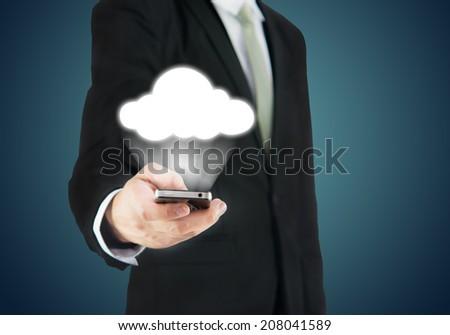 Businessman hand holding smart phone cloud connectivity on drak background - stock photo