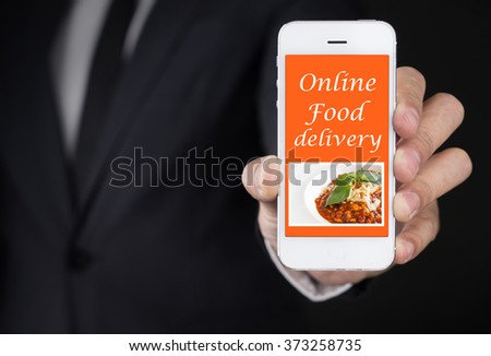 Businessman hand Holding Smartphone with Online food delivery on screen.lifestyle concept - stock photo
