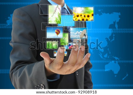 businessman hand holding streaming images virtual buttons - stock photo