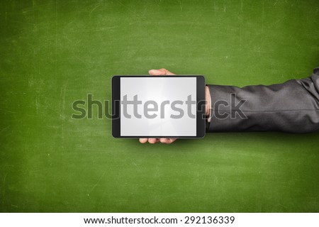 Businessman hand holding tablet front of empty blackboard - stock photo