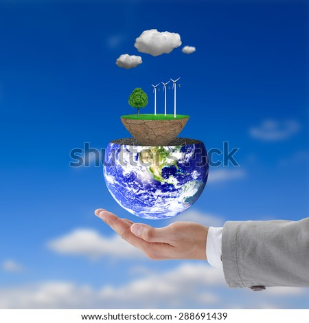 Businessman hand holding wind power station mills and trees on the lawn. Natural concept.  Elements of this image furnished by NASA. - stock photo