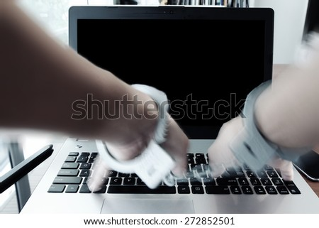 Businessman hand in handcuffs at wooden desk with laptop computer and digital tablet and stylus pen and smart phone as Cyber-Crime concept - stock photo