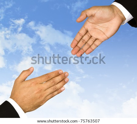 Businessman  hand is reaching out in the sky for help - stock photo