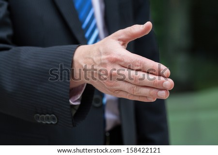 Businessman hand just before a handshake on green natural background