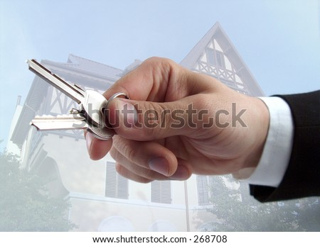 businessman hand offering keys house in the background - stock photo
