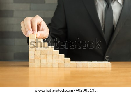 Businessman hand placing wood block on the top of stair. Business growth concept