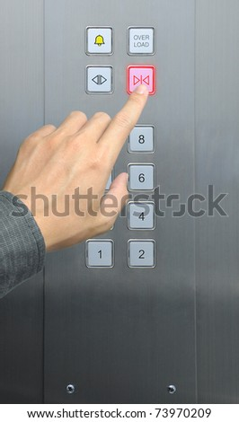 businessman hand press close door button in elevator - stock photo
