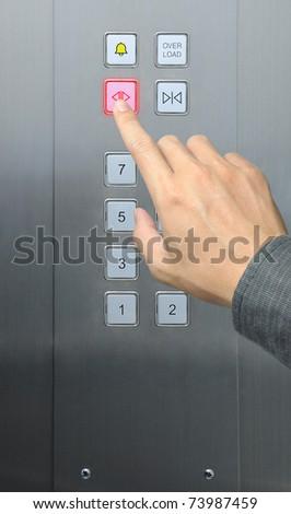 businessman hand press open door button in elevator - stock photo