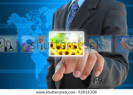businessman hand pressing a button streaming images on a touch screen interface - stock photo