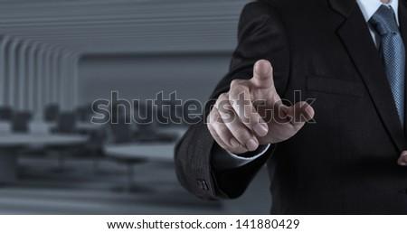 Businessman hand pressing an imaginary button on virtual screen - stock photo