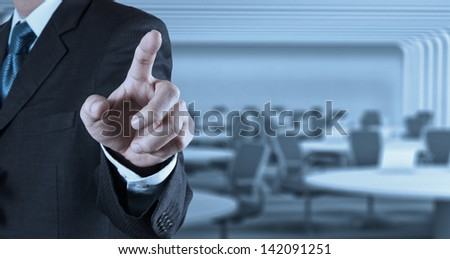 Businessman hand pressing an imaginary button on virtual screen - stock photo