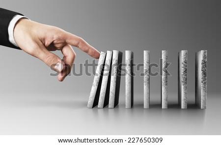 Businessman hand pushing domino - stock photo