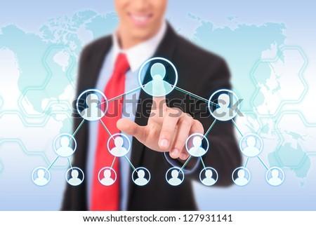 businessman hand pushing social network on world map - stock photo