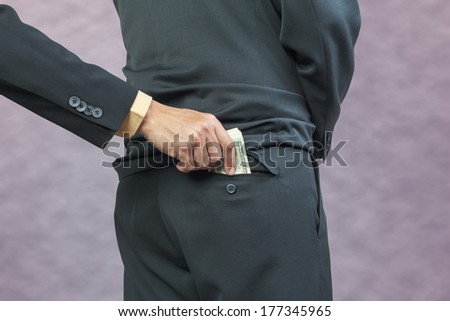 businessman hand put money to back pocket, finance corruption concept - stock photo