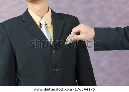 businessman hand put money to pocket, finance corruption concept - stock photo