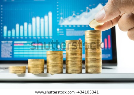Businessman hand putting gold coin to stack growing with financial graph chart on laptop screen.For business growth and financial concept - stock photo