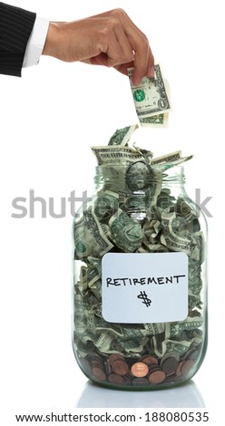 Businessman hand putting money into a glass jar full of money - stock photo