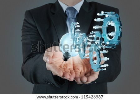 businessman hand show light bulb and gear to success as concept