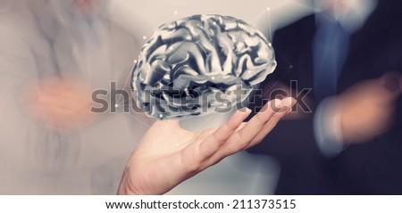 businessman hand showing 3d metal human brain as concept - stock photo