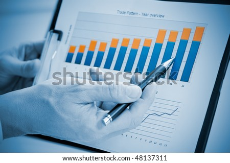 Businessman hand showing growing chart on annual report, good business growth - stock photo
