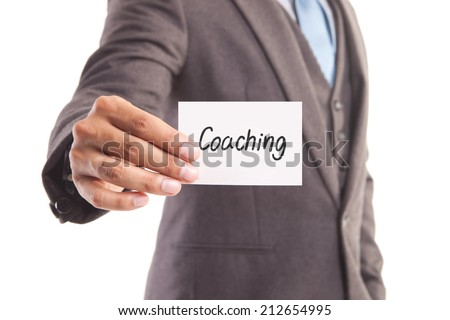 "Businessman hand showing someone his business card with""Coaching"" message - stock photo"