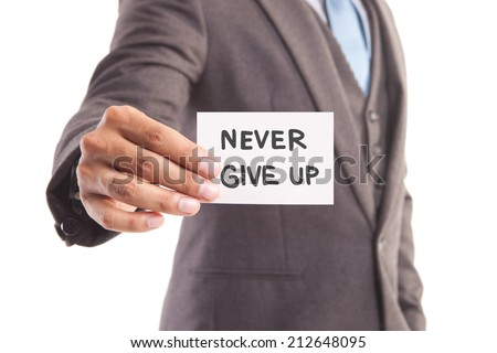 """Businessman hand showing someone his business card with""""never give up"""" message - stock photo"""