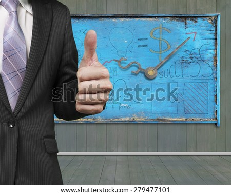 Businessman hand showing thumb up with business concept doodles on old blue weathered noticeboard background - stock photo