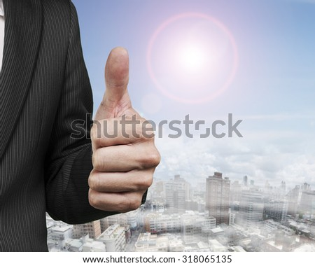 Businessman hand showing thumb up, with sun sky clouds cityscape background. - stock photo