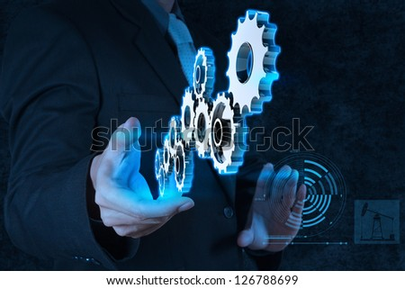 businessman hand shows gear to success  as concept - stock photo