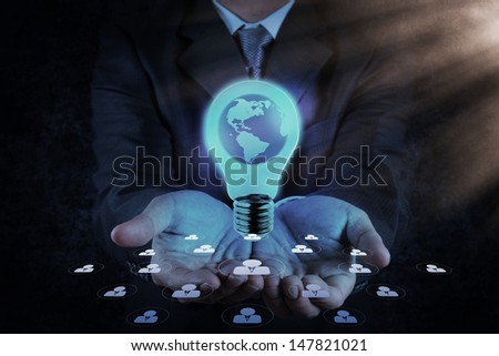 Businessman hand shows Light bulb with planet Earth as concept - stock photo