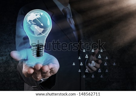 Businessman hand shows Light bulb with planet Earth social network as concept - stock photo