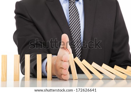 businessman hand stop dominoes continuous toppled  - stock photo