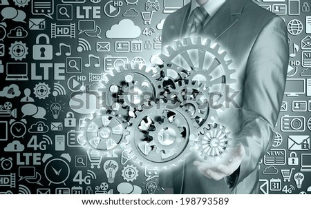 businessman hand touch blue gear to success as concept - stock photo